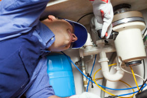 plumber repairing a broken garbage disposal in Long Beach, CA